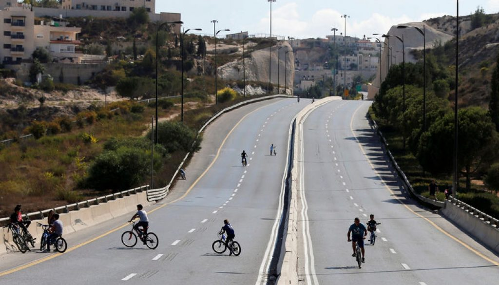 Children ride their bicycles in an empty street in Jerusalem during the Jewish holiday of Yom Kippur